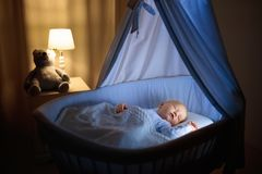 Baby boy drinking milk in bed. Adorable baby drinking milk in blue bassinet with canopy at night. Little boy in pajamas with formula bottle getting ready to Royalty Free Stock Photography