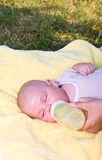 Baby boy drinking milk from bottle. Mother give drink her son by feeding bottle Stock Photos