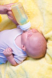 Baby boy drinking milk from bottle. Mother give drink her son by feeding bottle Stock Photo