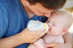 Baby boy drinking milk from bottle Stock Photos
