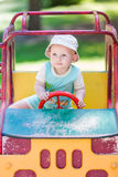 Baby boy driving a toy car at the playground. Outdoor Stock Photo