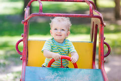 Baby boy driving a toy car at the playground. Outdoor Royalty Free Stock Photos