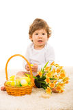Baby boy with Easter eggs. Baby boy sitting on fur carpet with basket with Easter eggs and daffodils Royalty Free Stock Photography