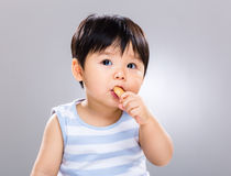 Baby boy eat biscuit and look away Stock Images