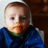 Baby boy eating. Little baby boy eating carrot all over his face Royalty Free Stock Image