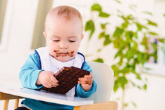 Baby boy eating chocolate Stock Photos
