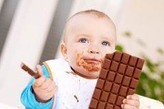 Baby boy eating chocolate Royalty Free Stock Photos