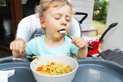 baby boy eating dinner outside house Royalty Free Stock Photo