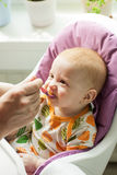 Baby boy eating first solid food from a spoon with g Stock Image