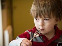 Boy eating in a restaurant Stock Photos