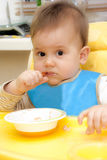 Baby boy eating in high chair Stock Photo