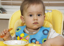Baby boy eating in high chair Royalty Free Stock Images