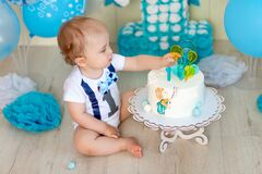 Baby boy eating his cake with his hands, baby 1 year old, happy childhood, children`s birthday