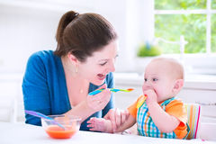 Baby boy eating his first solid food with his mother. Young attractive mother feeding her cute baby son, giving him his first solid food, healthy vegetable pure Royalty Free Stock Photo