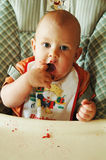 Baby boy eating by itself stock photo