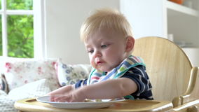 Baby Boy Eating Meal In In High Chair Stock Photos