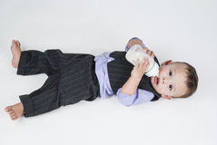 Baby boy eating milk from the bottle. In the center of this horizontal image a small child lying down  on the white floor and white background on his back. the Stock Photos
