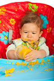 Baby boy eating puree. Messy baby boy eating puree by yourself and sitting in chair Stock Photo