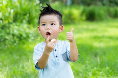Baby boy eating with snack and showing thumb up. Asian young little boy at outdoor stock images