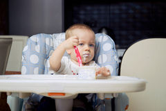 Baby boy eating yoghurt cream Stock Image