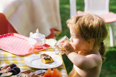 Baby boy eats dessert. Sweet baby boy blond kid eats delicious dessert cake and drinks juice on sunny summer day on natural background Stock Photo