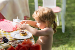 Baby boy eats dessert. Sweet baby boy blond kid eats delicious dessert cake and drinks juice on sunny summer day on natural background Stock Images
