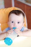 Baby boy eats from small bottle Royalty Free Stock Images