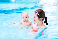 Baby boy enjoying swimming lesson in pool with mother stock image