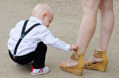 Baby boy examines female shoes Stock Photo