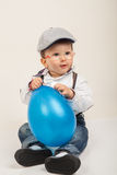 Baby boy with eyeglasses and hat playing with blue balloon royalty free stock photography