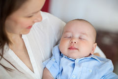 Baby boy falling asleep in the arms of her mother Royalty Free Stock Photos