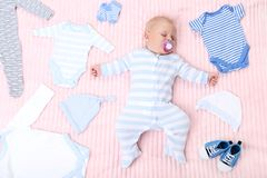 Baby boy with fashion clothes. Lying on pink bed royalty free stock image
