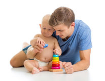 Baby boy and father play together with pyramid toy Stock Image