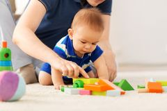 Baby boy with father playing toy blocks at home stock photos