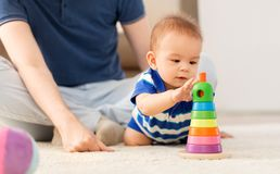 Baby boy with father and pyramid toy at home royalty free stock image