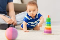 Baby boy with father and pyramid toy at home royalty free stock photos