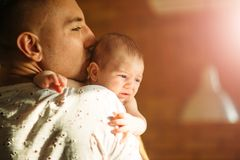 Baby boy on father`s shoulder. Sweet baby boy on daddy shoulder, father talking on phone Stock Images