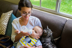 Baby boy fed by a pretty young woman. Cute baby boy being fed milk by a pretty young women in a home setting stock images