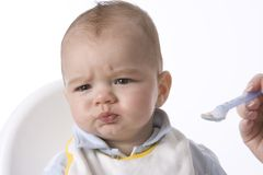 Baby Boy Is Fed With A Spoon. And Has A Disapproving Expression stock images