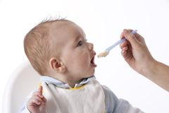 Baby Boy Is Fed With A Spoon. On white background Royalty Free Stock Photos