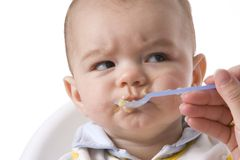 Baby Boy Is Fed With A Spoon. And Has A Disapproving Expression Stock Image