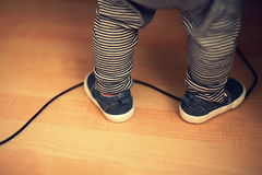 Baby boy feet standing on a power cord. At home Royalty Free Stock Photo