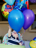 Baby Boy first birthday balloons. Cute baby boy reaching for his birthday balloons stock image