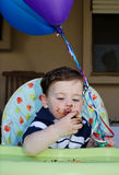 Baby Boy first birthday. Cute messy baby boy eating a cake at his first birthday party Stock Photo