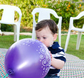 Baby Boy first birthday. Cute baby boy playing with a purple balloon royalty free stock image