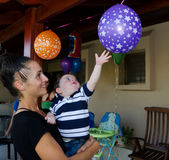 Baby Boy first birthday party. Cute baby boy reaching for a balloon at his first birthday stock photo