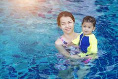 Baby boy first time in a swimming pool Stock Image