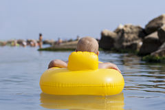 Baby boy floating on sea Stock Image