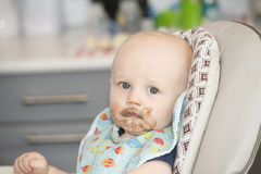 Baby Boy with Food on his Face in a High Chair Royalty Free Stock Photos