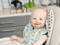 Baby Boy with Food on his Face in a Highchair Royalty Free Stock Images